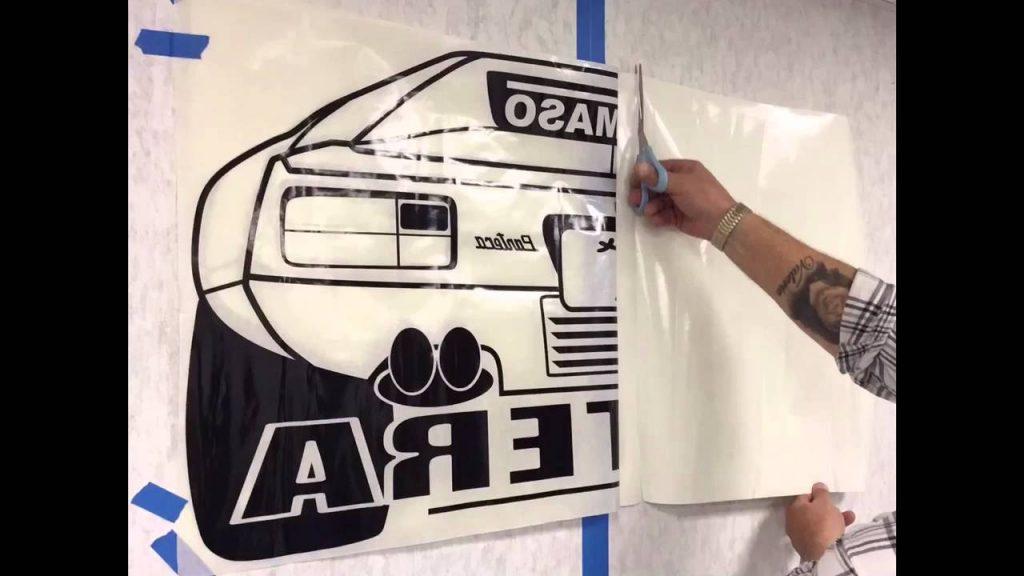 Met schilders tape een muursticker opplakken